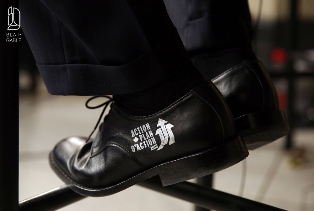 Canada's Finance Minister Flaherty wears the Economic Action Plan logo on his shoes during an interview after delivering the budget on Parliament Hill in Ottawa