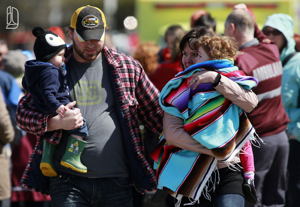 A man and a woman carry two small children away from the scene of a shooting