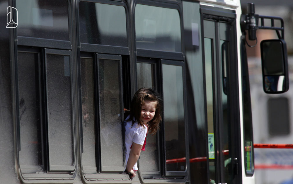 A young girl looks out a bus window while waiting for a caregiver