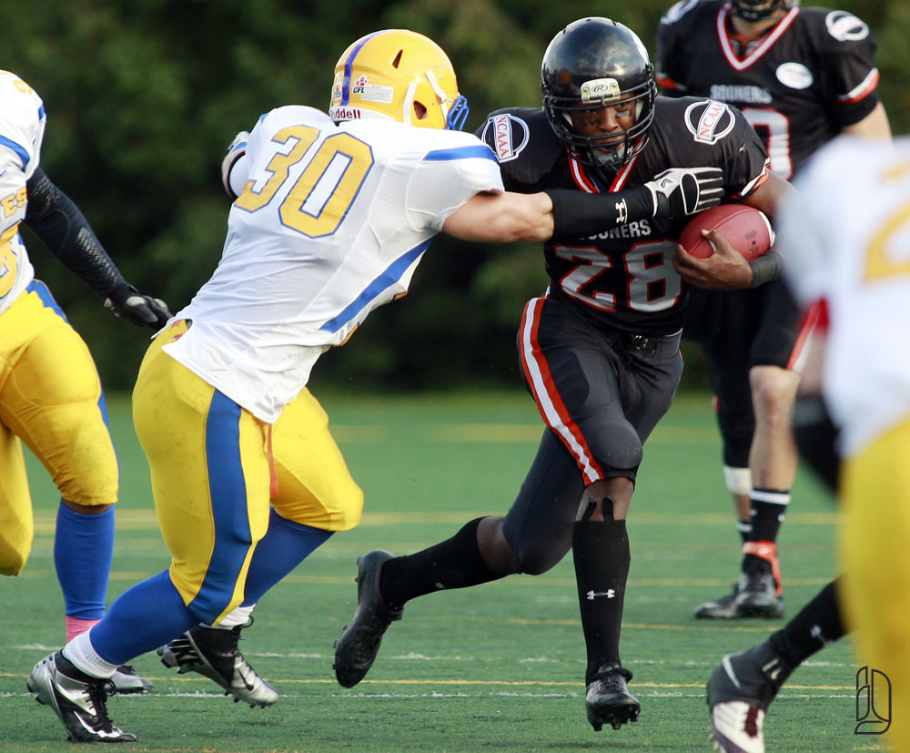 Ottawa Sooners Keith Graham evades tackle by Burlington Braves Richard Beckstead