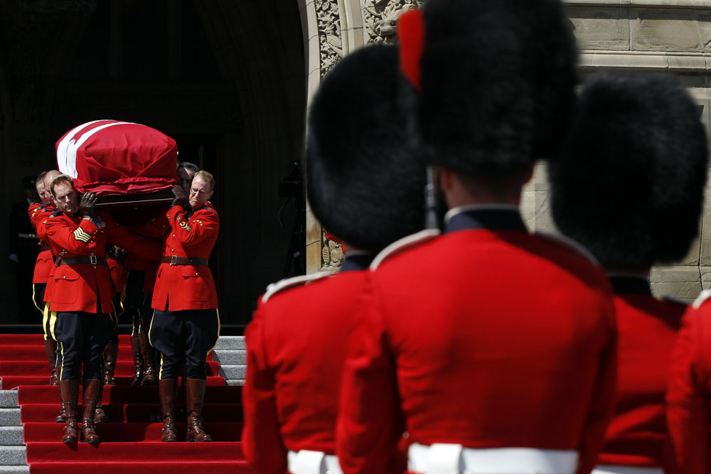 RCMP pallbearers remove the casket of NDP Leader Layton from Parliament Hill after lying in state in Ottawa