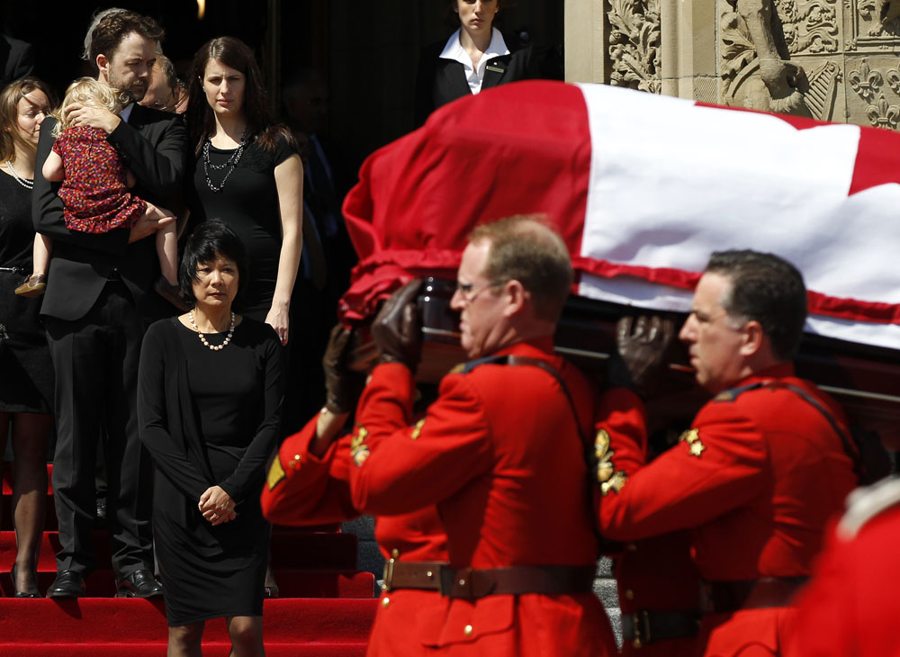 Chow, with family, watches as RCMP pallbearers remove the casket of her husband and NDP Leader Layton from Parliament Hill after lying in state in Ottawa