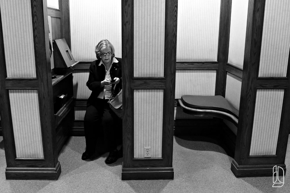 Green Party leader Elizabeth May composes a tweet from a pay phone booth
