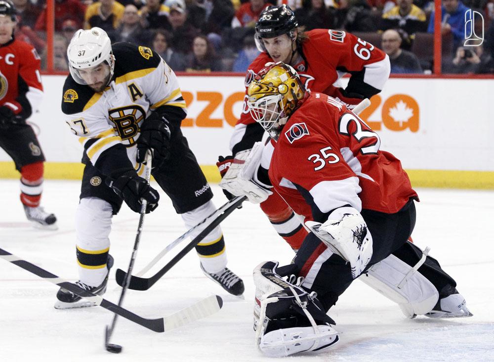 Boston Bruins' Bergeron shoots on Ottawa Senators' Auld and Karlsson