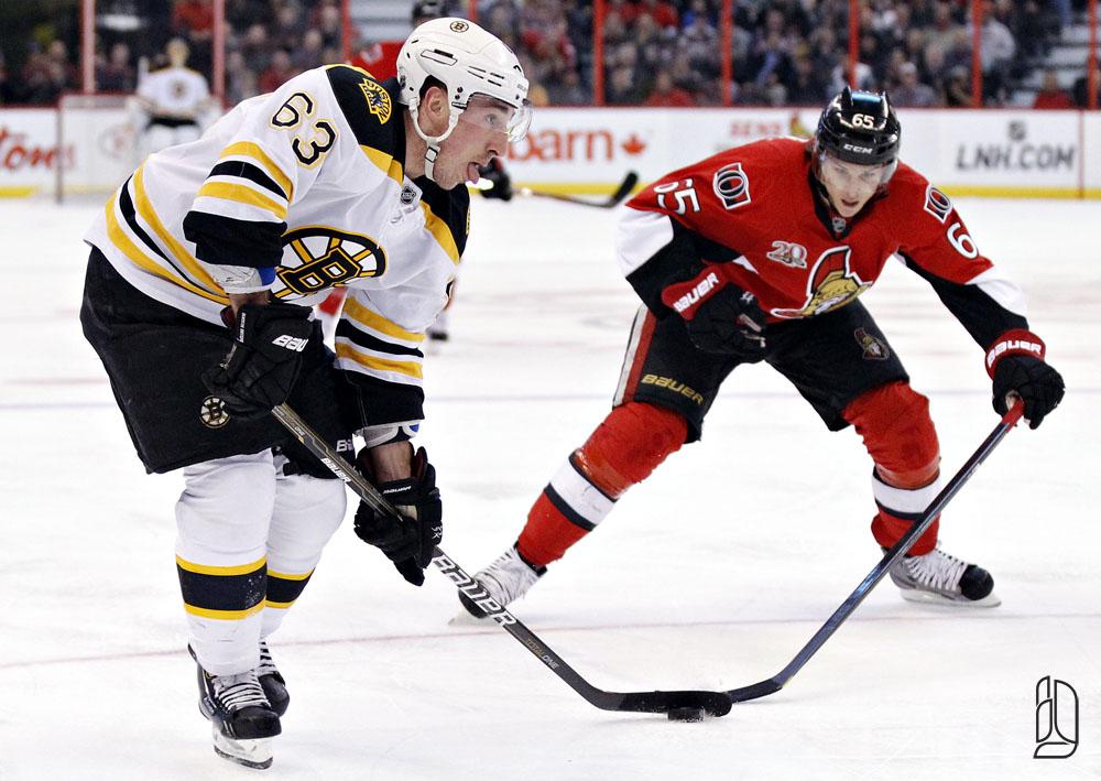 Ottawa Senators' Karlsson knocks the puck away from Boston Bruins' Marchand