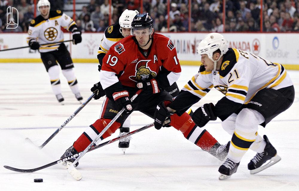 Ottawa Senators' Spezza moves the puck around Boston Bruins'  Lucic and Ference