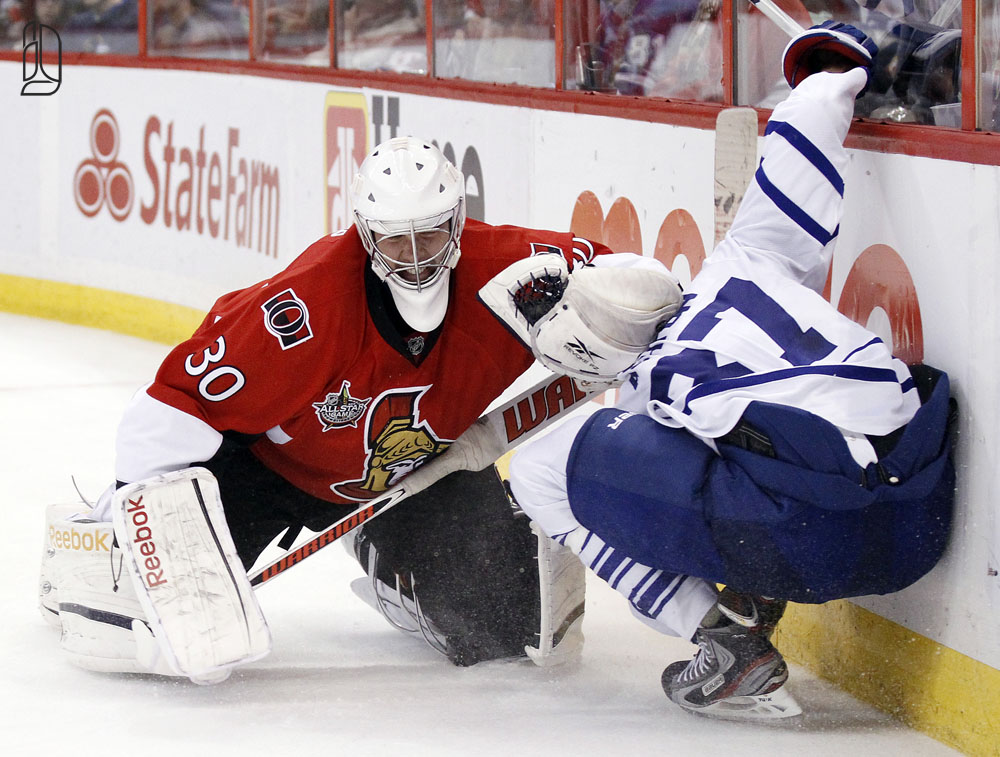 Senators' Bishop holds down Maple Leafs' Ashton behind the net